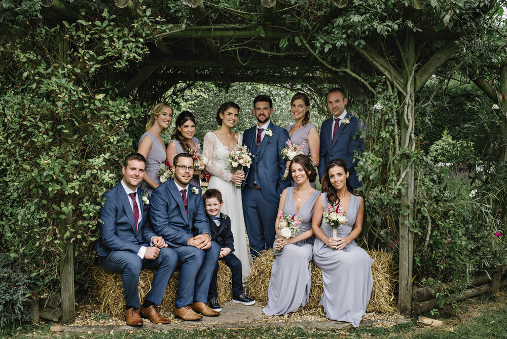 bridal party sitting on haystacks
